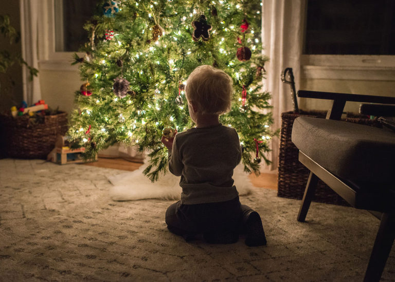 boy decorating tree in holiday tradition